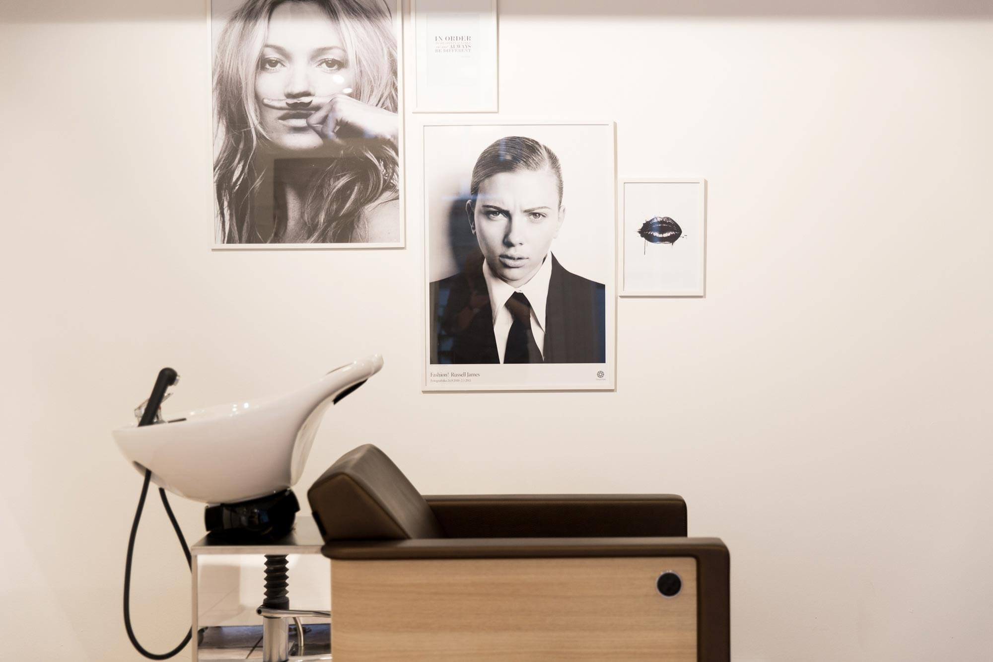 A picture of a wall in the salon with some pictures.